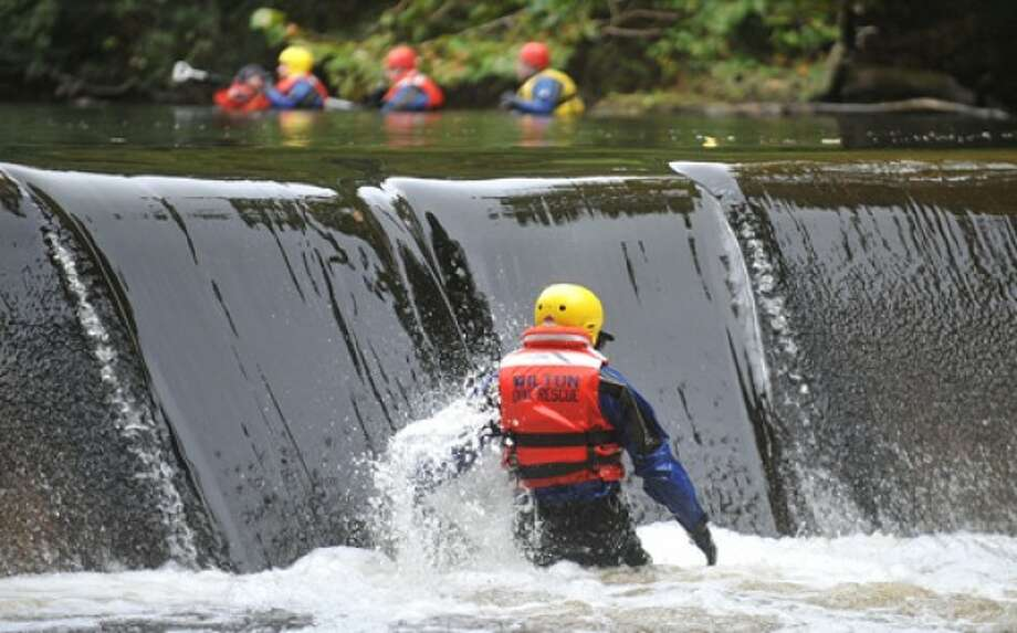 File Photo by Alex von Kleydorff. Wilton Dive Team member Firefighter Gary Pryor makes his way across the Norwalk river just under the lower dam as other team members search above, north of Merwin Meadows park looking for a missing man in October 2010.