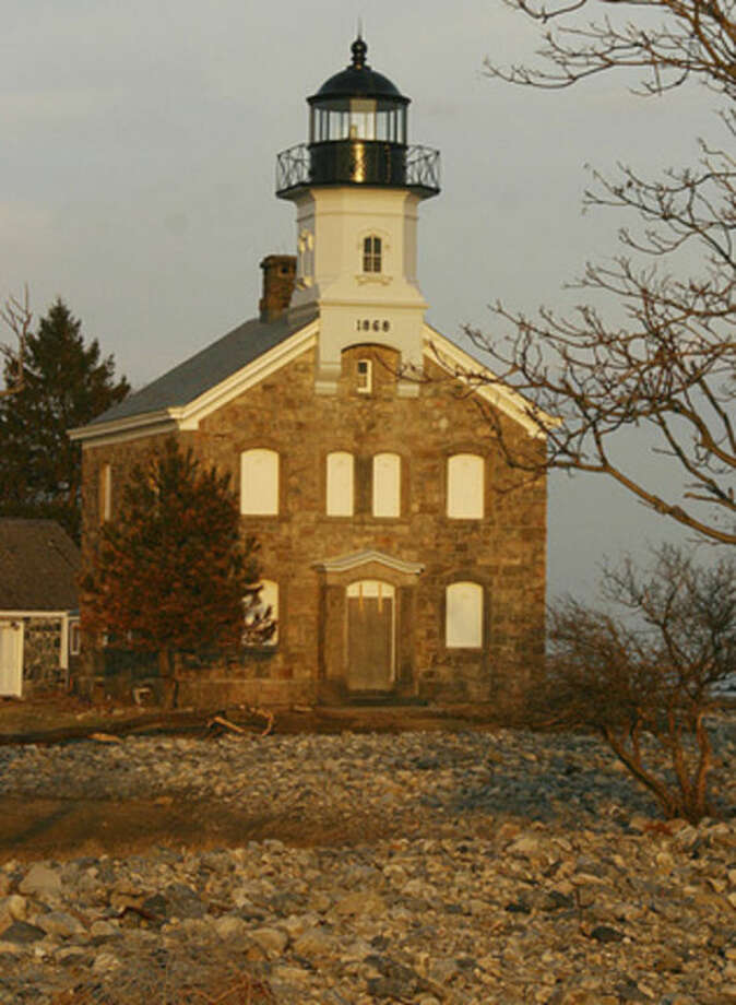 Hour photo / Chris BosakSheffield Island Lighthouse with rock strewn about the lawn from Hurricane Sandy.