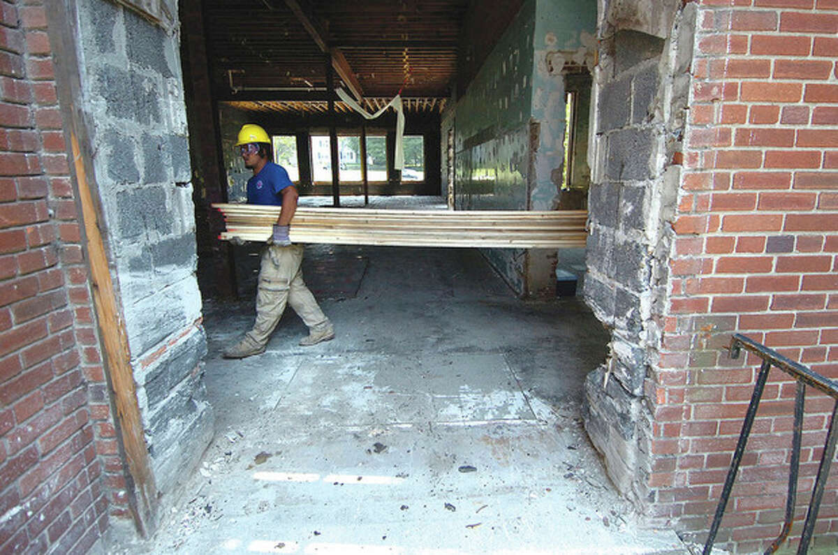 Hour photo/Alex von Kleydorff Top and bottom photos: workers with Maggiore Construction work on the interior of the old Fitch School this week.