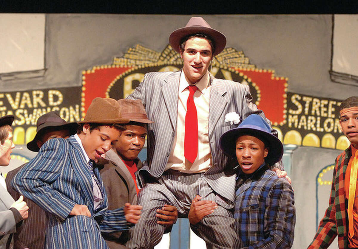 """Hour photo / Alex von Kleydorff Mackenzie Raub (center) as Nathan Detroit in """"Guys and Dolls"""" at Brien McMahon High School. The show opens Friday at 8 p.m. with two shows Saturday at 2 p.m. and 8 p.m. and another 2 p.m. show on Sunday. Tickets can be purchased at the door and will cost students and seniors $10 and adults $15. VIP seats that """"get you right in front, where you will see the actors sweat you'll be so close,"""" are available for $20."""