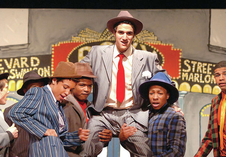 "Hour photo / Alex von KleydorffMackenzie Raub (center) as Nathan Detroit in ""Guys and Dolls"" at Brien McMahon High School. The show opens Friday at 8 p.m. with two shows Saturday at 2 p.m. and 8 p.m. and another 2 p.m. show on Sunday. Tickets can be purchased at the door and will cost students and seniors $10 and adults $15. VIP seats that ""get you right in front, where you will see the actors sweat you'll be so close,"" are available for $20. / 2013 The Hour Newspapers"