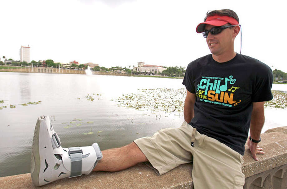 In this photo taken Thursday, April 19, 2012, Greg Farris takes a break while wearing a protective boot as he helps set up for a weekend triathlon event in Lakeland, Fla. Farris injured his foot while running in barefoot running shoes.(AP Photo/John Raoux) / AP