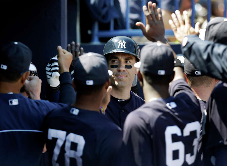 New York Yankees designated hitter Travis Hafner, center, is congratulated in the dugout after hitting two-run, home run in the third inning of a spring training baseball game against the Miami Marlins in Tampa, Fla., Friday, March 15, 2013. The Yankees defeated the Marlins 7-3. (AP Photo/Kathy Willens) / AP
