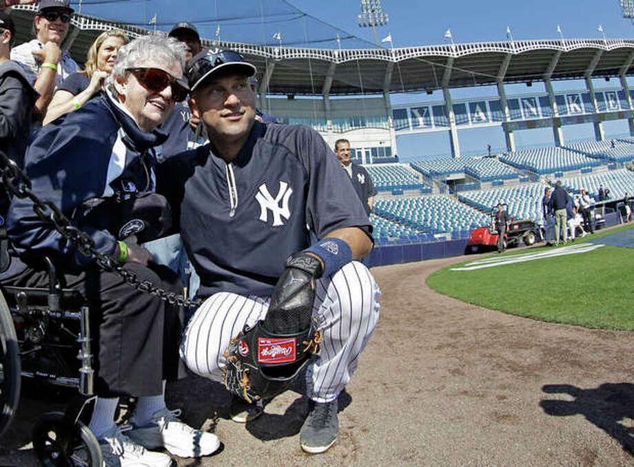 New York Yankees shortstop Derek Jeter poses for a photograph with 85-year-old New York Yankees fan Annie Economy from Eagle Rock, Va., before a spring training baseball game in Tampa, Fla., Friday, March 15, 2013. (AP Photo/Kathy Willens) / AP