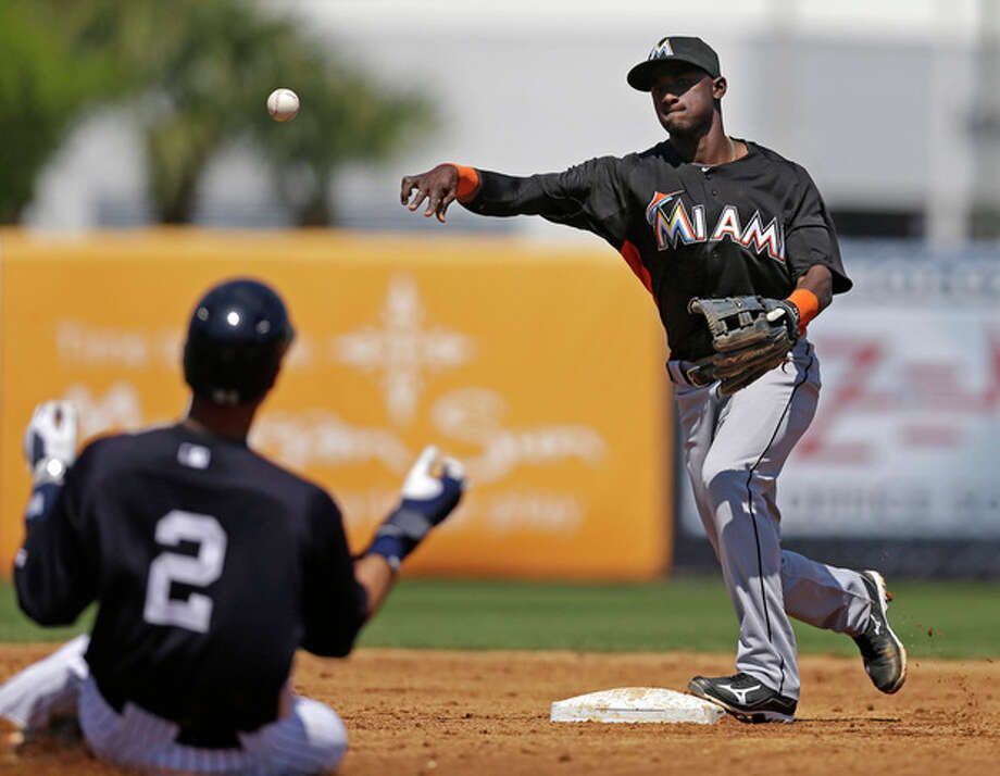 Miami Marlins shortstop Adeiny Hechavarria, right, puts out New York Yankees Derek Jeter (2), who avoids a hard slide as Yankees Ichiro Suzuki (not shown) hit into a third-inning fielder's choice in a spring training baseball game in Tampa, Fla., Friday, March 15, 2013. (AP Photo/Kathy Willens) / AP