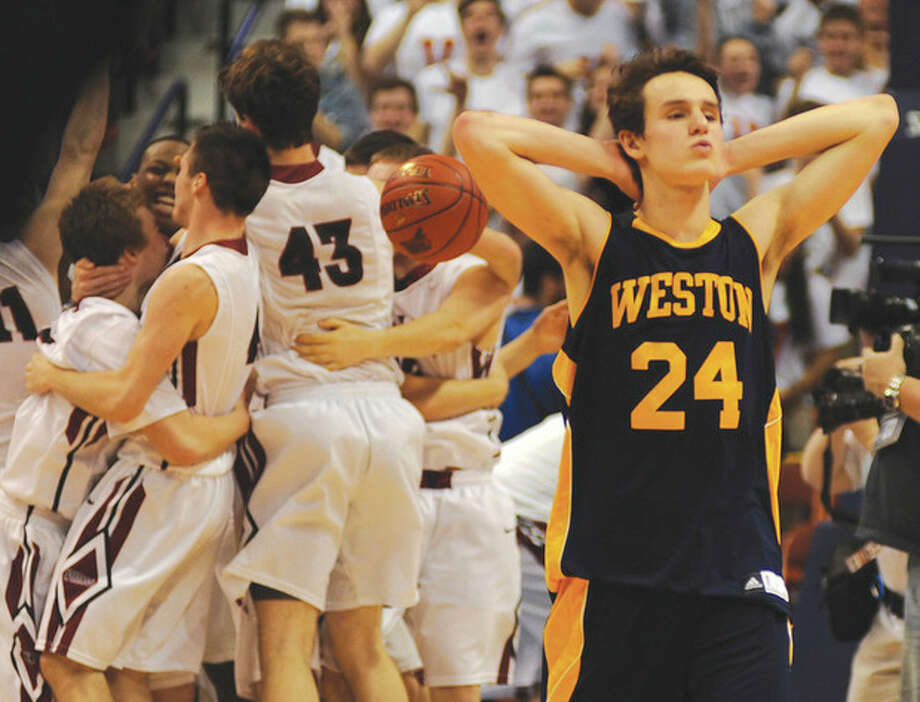Hour photo/John NashWeston's Charlie DiPasquale (24) walks off the court as the Valley Regional Warriors begin to celebrate their Class M state championship game win at Mohegan Sun Arena on Friday night. Trailing at halftime, the fifth-seeded Panthers surged to a 52-45 victory.