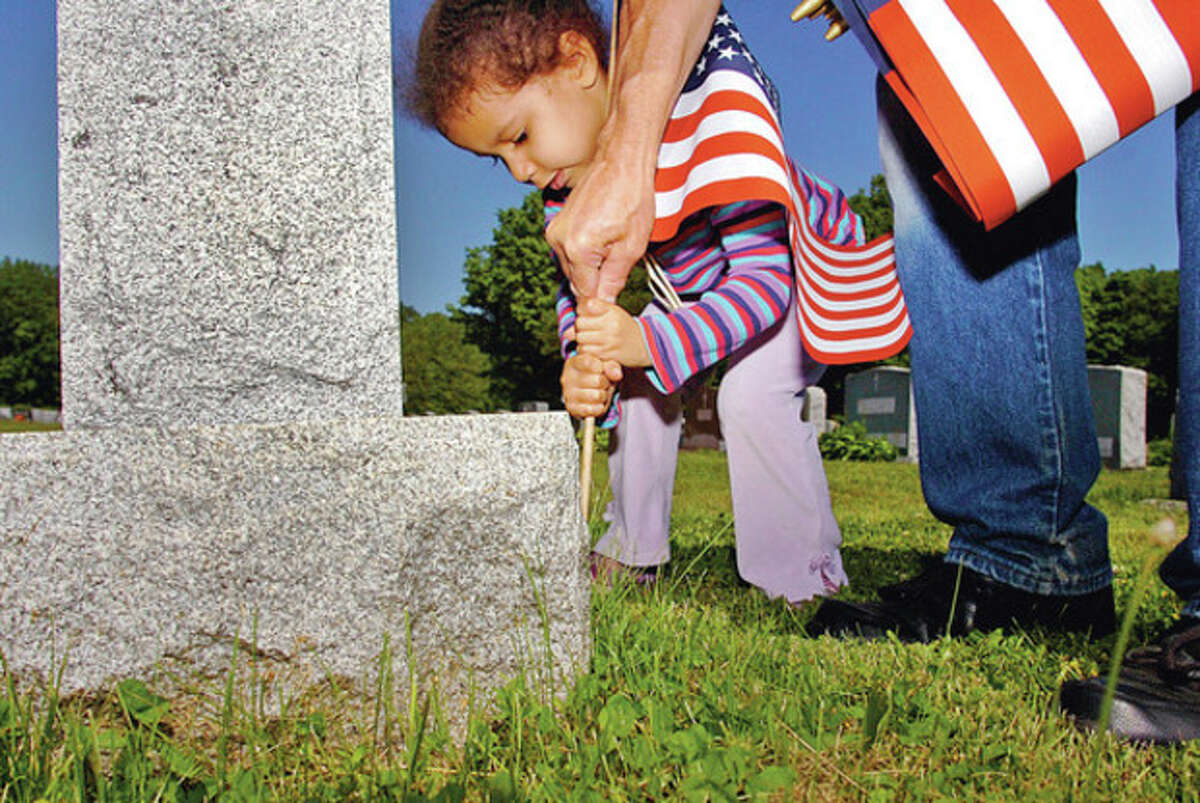 Abby Kelly, 4, get help planting a flag during the Northrop Grumman sponsored flag-placing ceremony for veterans' graves at St. John's Cemetery in Norwalk Saturday. Hour photo / Erik Trautmann