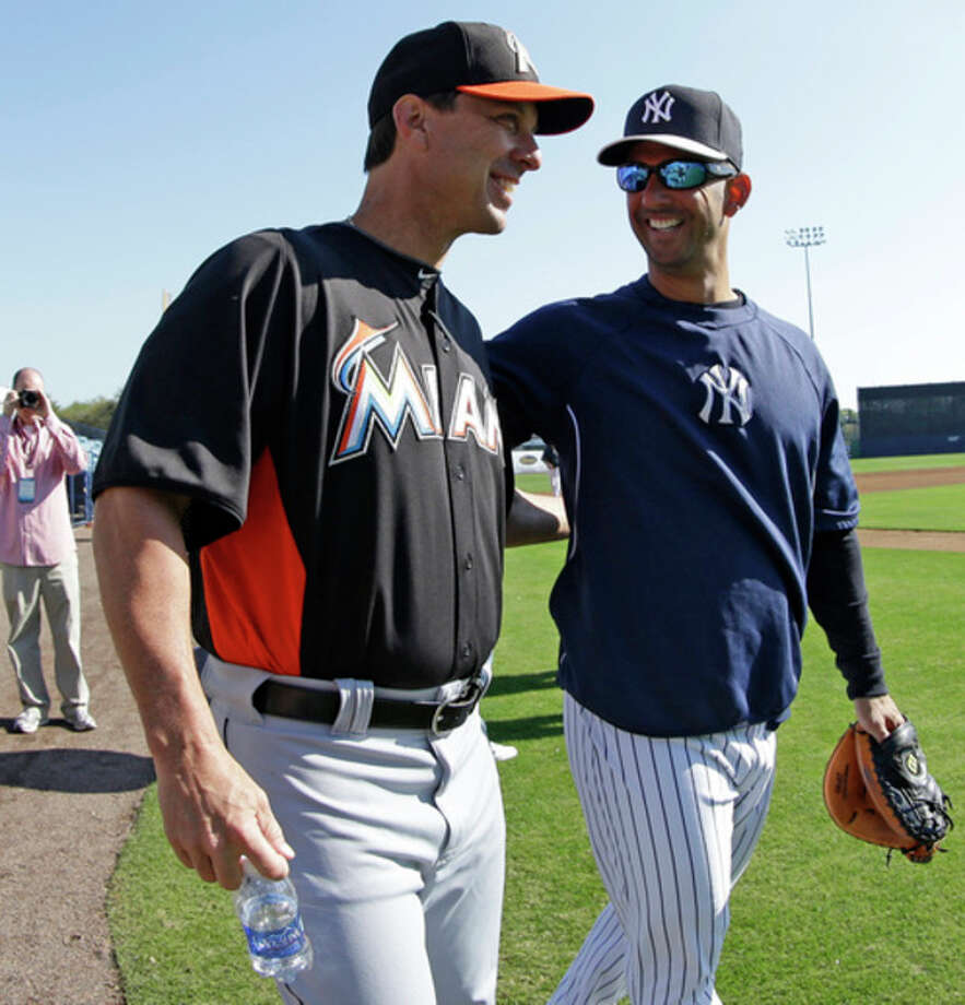 Miami Marlins hitting coach Tino Martinez, left, chats with former Yankees catcher and current Yankees guest instructor Jorge Posada on the field before a spring training baseball game between the Marlins and the Yankees in Tampa, Fla., Friday, March 15, 2013. (AP Photo/Kathy Willens) / AP