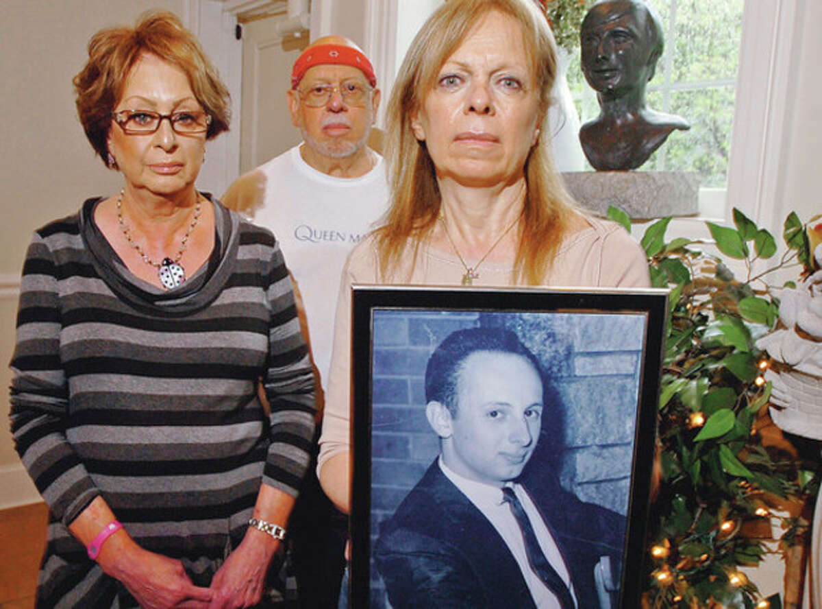 Photos by Erik Trautmann Siblings of the late Joseph Pelicci, from left, Fran Gross, Anthony Pelicci and Toni Lupinacci, display a portrait of their brother as they hope for his 1973 murder case to be turned over to the Stamford jurisdiction. Below, Stamford Police Sgt. Anthony Lupinacci holds a 1973 newspaper containing an article on the disappearance of Joseph Pellici.
