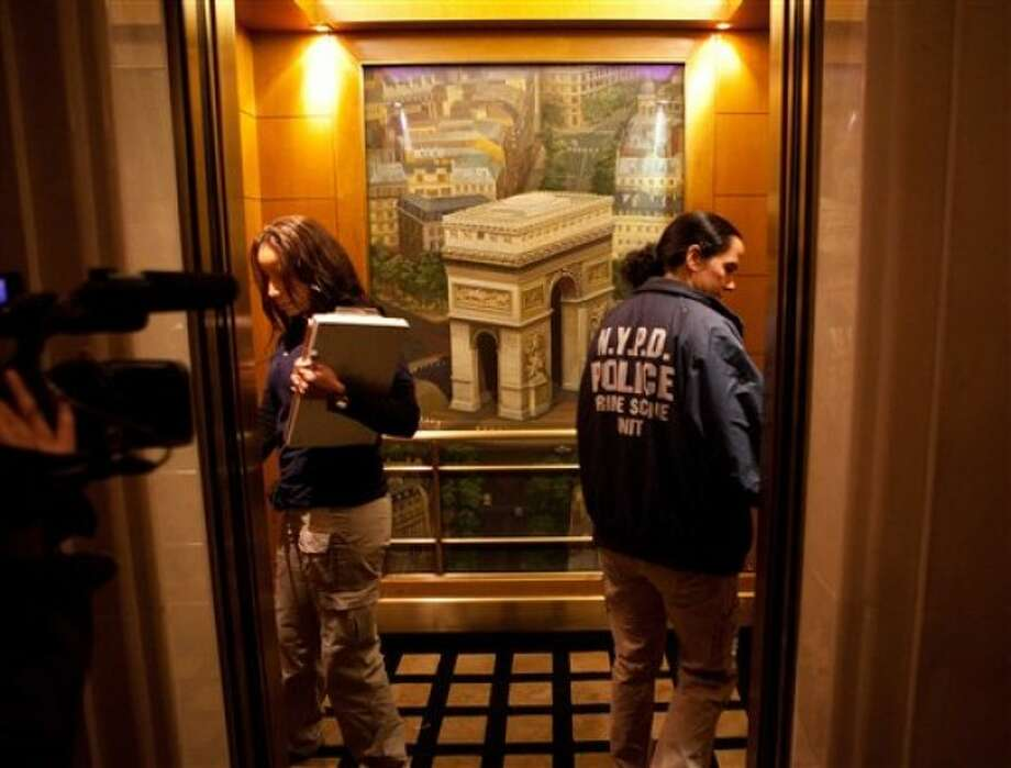 Two members of the NYPD crime scene unit enter an elevator at the Sofitel hotel in New York, Saturday, May 14, 2011. Dominique Strauss-Kahn, the leader of the International Monetary Fund and a possible candidate for president of France, was pulled from an airplane moments before he was to fly to Paris and was being questioned Saturday by police in connection with the violent sexual assault of a hotel maid from the Sofitel, police said. (AP Photo/John Minchillo)