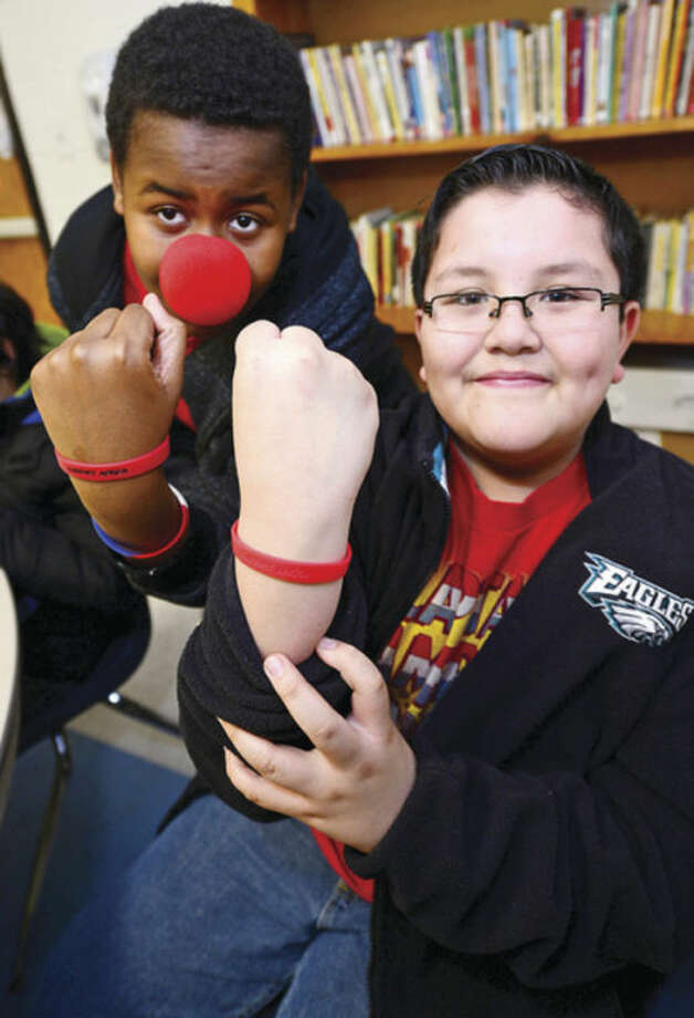 "Roton Middle School seventh-grader Ethan Mills sells a red braclet to sixth-grader Enrique Arriaga during ""Red Nose Day"" a ""fun""raiser to raise awarness for African children with malaria.Hour photo / Erik Trautmann"