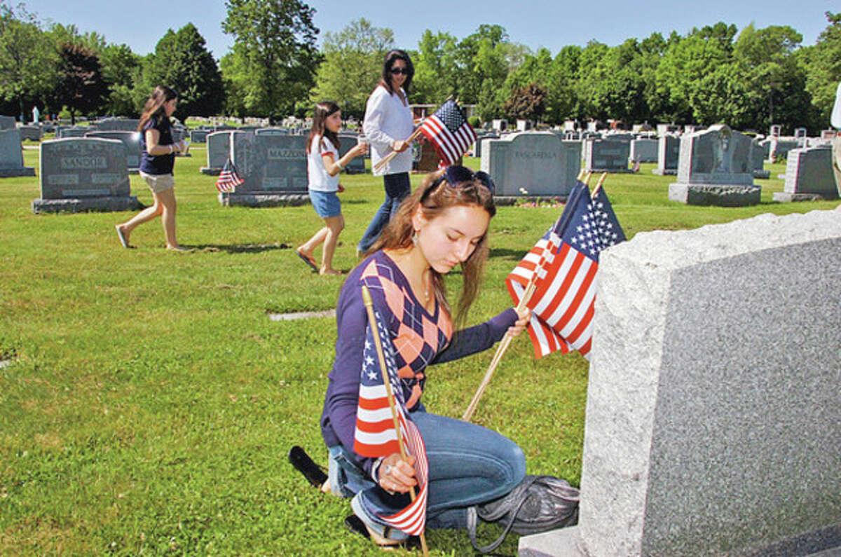 Christina Breisler plants a flag during the Northrop Grumman sponsored flag-placing ceremony for veterans' graves at St. John's Cemetery in Norwalk Saturday. Hour photo / Erik Trautmann