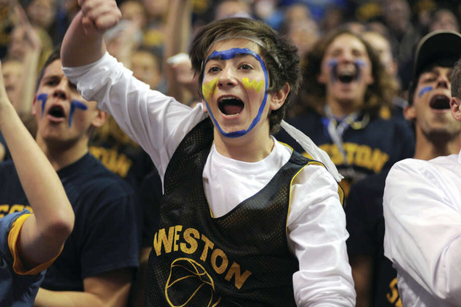 Weston High School freshman Spencer Quist and his fellow Trojans student body members erupt as their basketball team is introduced before the start of the CIAC Class M championship game on Friday night at the Mohegan Sun.