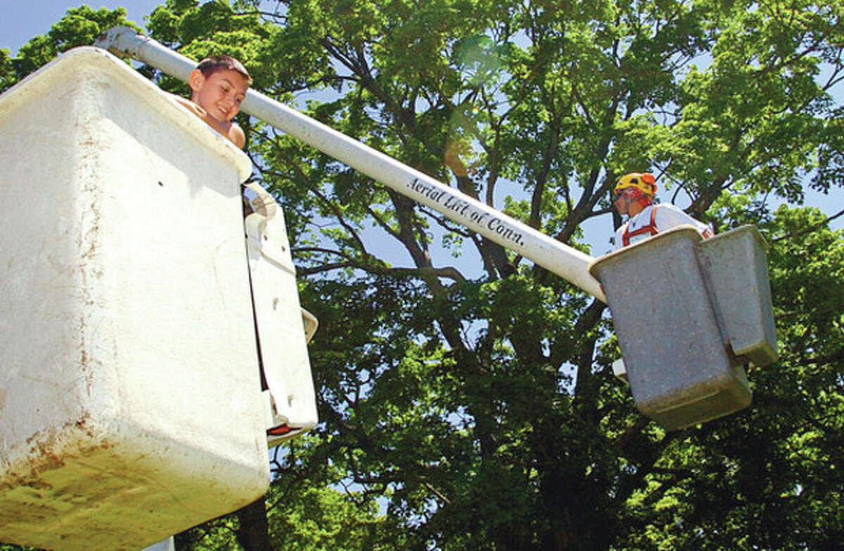 11 year old Peter Baez gets brought up in a bucket lift at the Norwalk-Wilton Tree Festival Saturday in Cranbury Park. Hour photo / Erik Trautmann