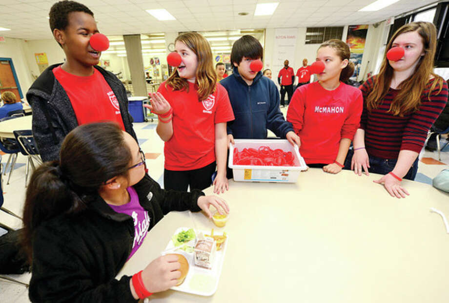 """Hour photos / Erik TrautmannAbove, Roton Middle School sixth-grader Kaili Chan listens to seventh-graders Ethan Mills, Grace O'Malley, Alberto Regalado, Alison Coutts and Ellie Smith talk about their fundraising campaign """"Red Nose Day"""" to raise awarness for African children with malaria. Below, seventh-grader Ethan Mills sells a red braclet to sixth-grader Enrique Arriaga / (C)2013, The Hour Newspapers, all rights reserved"""