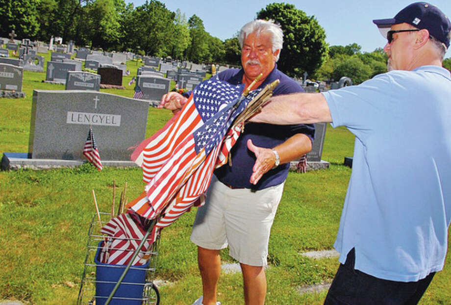 Ed Isaacs recieves old flags from Paul Sullivan Northrop Grumman sponsored flag-placing ceremony for veterans' graves at St. John's Cemetery in Norwalk Saturday.Hour photo / Erik Trautmann / (C)2012, The Hour Newspapers, all rights reserved