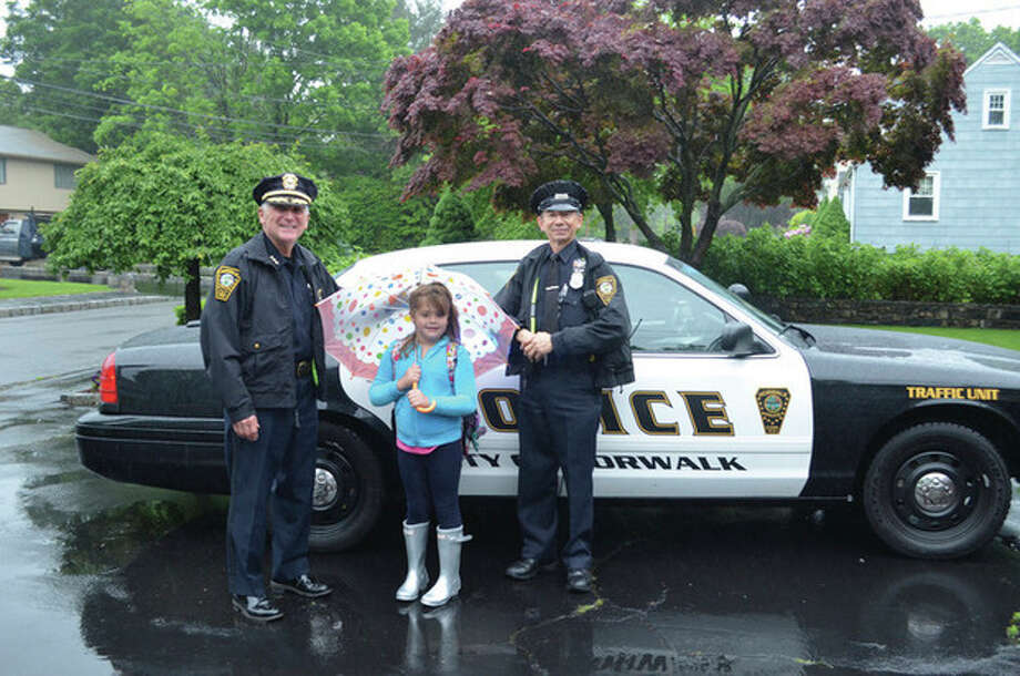 Contributed photoNorwalk Police Chief Harry Rilling, left, and Officer Cesar Ramirez gave Kadence Faucher a ride to and from school with lights and sirens turned on Tuesday.