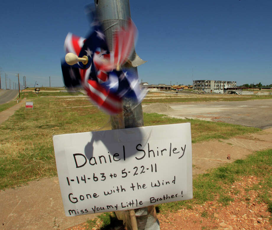 A sign remembering a tornado victim is seen on a street corner Tuesday, May 22, 2012, in Joplin, Mo. The community is marking the anniversary of an EF-5 tornado that killed 161 people as it cut a wide swath through Joplin a year ago. (AP Photo/Charlie Riedel) / AP