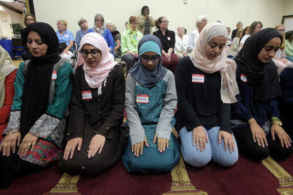 Non-Muslim members of the community observe a special prayer Monday at a Muslim community center in Longwood, Fla.