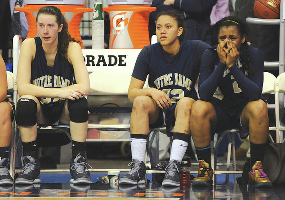Hour photo/John NashThe Norwalk trio of ,from left, Aly Furgiuele, Briana Mann and Jovan Kingwood, who all start for the Notre Dame-Fairfield girls basketball team, sit on the bench as the final seconds tick off in Friday night's CIAC Class M girls basketball championship game at the Mohegan Sun Arena. Unbeaten Cromwell beat the Lancers, 42-28.
