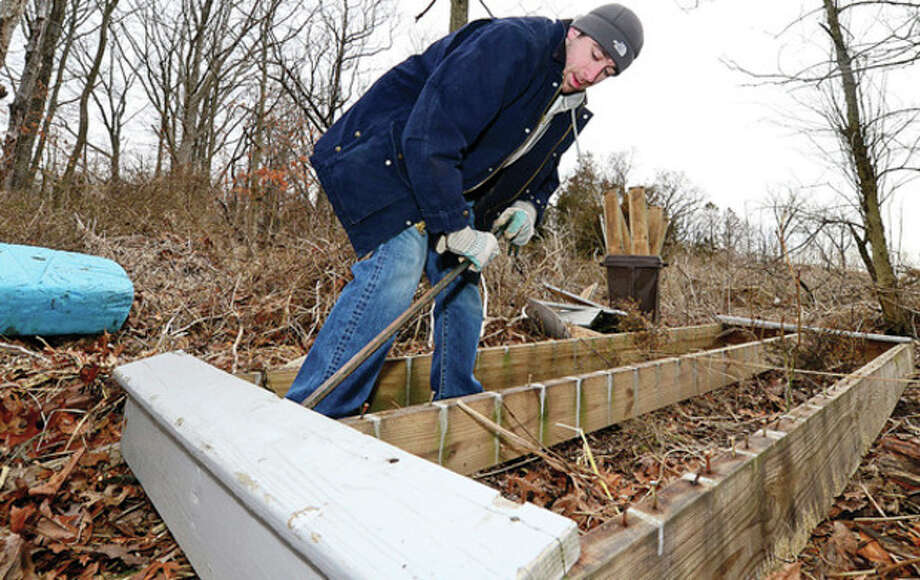 Nick Kantor takes apart a dock that washed up on Hart Peninsula during The Norwalk Land Trust (NLT) major storm cleanup at Farm Creek Preserve on Sammis Street in RowaytonSaturday.Hour photo / Erik Trautmann / (C)2013, The Hour Newspapers, all rights reserved