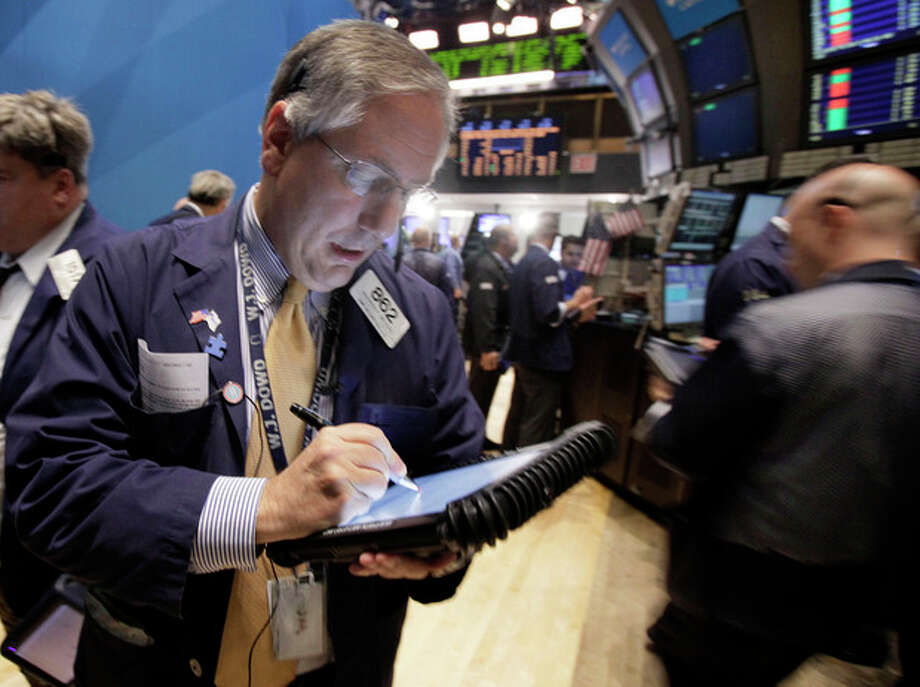 Trader Warren Meyers, left, works on the floor of the New York Stock Exchange Monday, Nov. 7, 2011. Stocks edged higher in choppy trading Monday as investors turned their attention toward mixed headlines out of Europe. (AP Photo/Richard Drew) / AP
