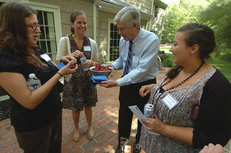 Photo by Alex von Kleydorff. Wilton Superintendent of Schools Gary Richards serves some fresh grapes to new teachers, from left, Melissa Pulito, Kristen Darash and Meredith Walker, at a reception at his home on Monday. / 2011 The Hour Newspapers