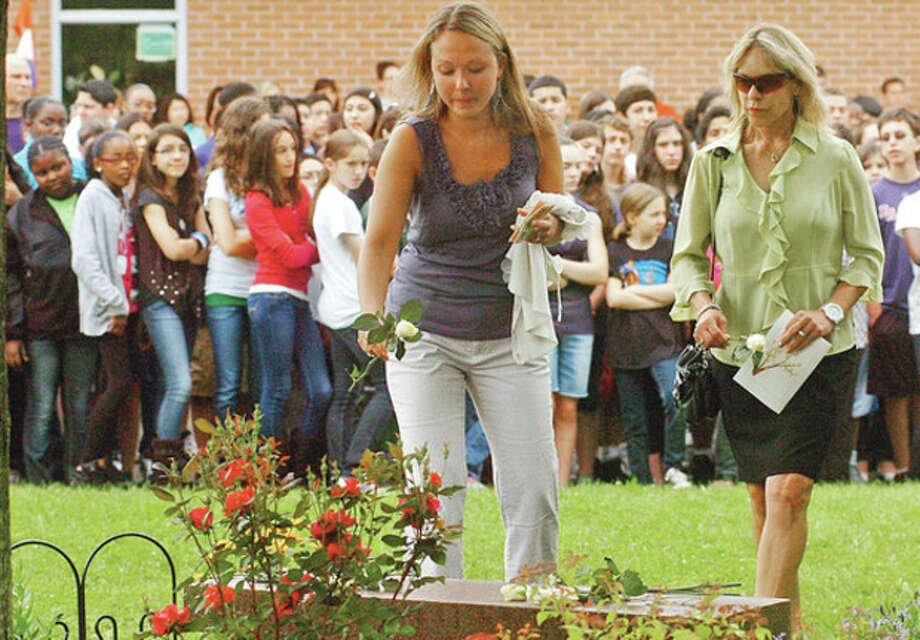 West Rocks Middle School teacher Marisa Novotny places a rose at a dedication ceremony Wednesday morning for former teacher Carla Mortelliti, for whom a bench was placed outside the school in her honor. / (C)2012, The Hour Newspapers, all rights reserved