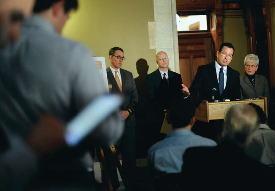 AP Photo / Jessica Hill Gov. Dannel P. Malloy, at podium, speaks to the media at the Capitol as budget chief Ben Barnes, left, state Comptroller Kevin Lembo, second from left, and Lt. Gov. Nancy Wyman, right, look on in Hartford Monday. / AP2012