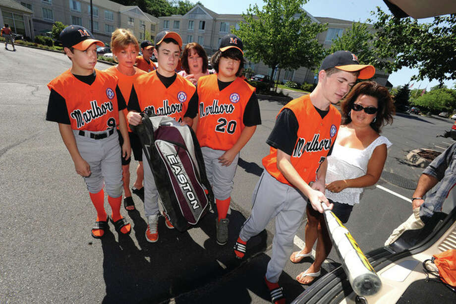 Hour photo / Matthew Vinci Members of the Marlboro, Mass., baseball team and families, staying at the Hilton Garden Inn, on Sunday morning prepare for a game vs. Norwalk for the Babe Ruth New England Tournament. From left, Kevin Falvey and his mom, Debrah, Tim Smith and his mom, Janet, Austin Echevarria, Ryan Gibbons and Mary Echevarria. / (C)2011, The Hour Newspapers, all rights reserved