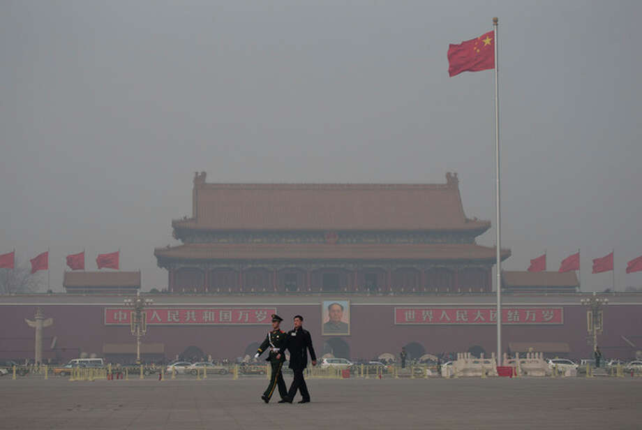 In this Friday, March 8, 2013 Chinese paramilitary policemen march across Tiananmen Square on a hazy day in Beijing, China. Facing public outrage over smog-choked cities and filthy rivers, China's leaders are promising to clean up its neglected environment, a pledge that sets up a clash with political pressures to keep economic growth strong. (AP Photo/Andy Wong) / AP