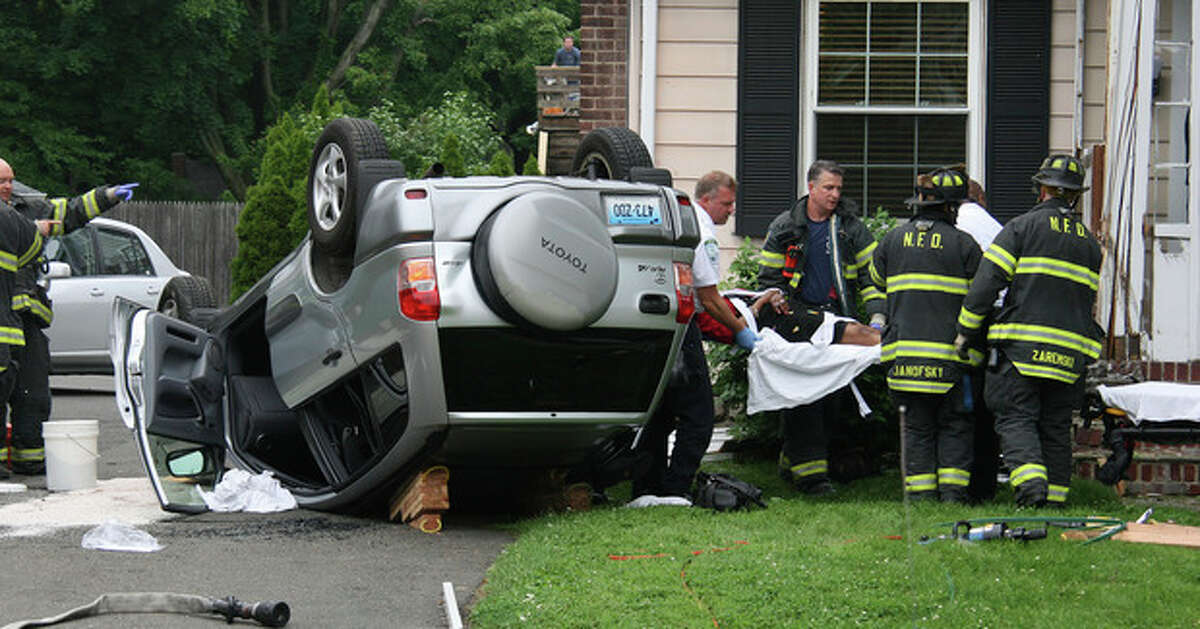 Hour photo / Chris Bosak Norwalk firefighters, EMS and police responded to a rollover at 197 East Ave. shortly before 5 p.m. on Friday. The drive of a Toyota Rav 4 drove off East Avenue and hit the brick porch of a house, causing the vehicle to roll over. The passenger was transported to Norwalk Hospital with abdominal pain.