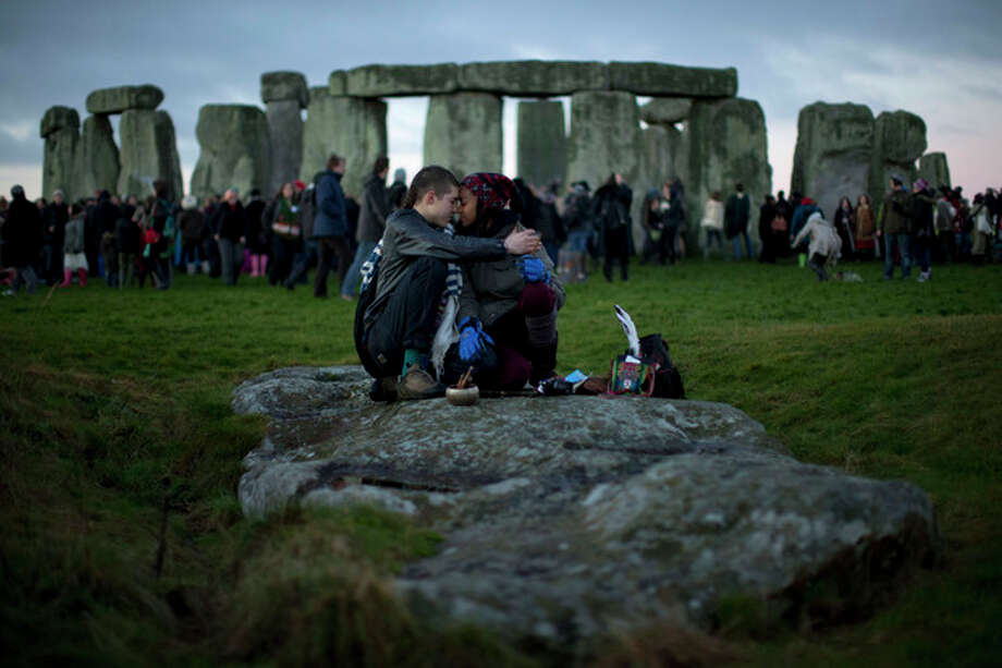 FILE - People embrace by the ancient stone circle of Stonehenge, in southern England, as access to the site is given to druids, New Age followers and members of the public on the annual Winter Solstice, in this Friday, Dec. 21, 2012 file photo. British researchers have proposed a new theory for the origins of Stonehenge: It may have started as a giant burial ground for elite families around 3,000 B.C. New studies of cremated human remains excavated from the site suggest that some 500 years before the Stonehenge we know today was built, a larger stone circle was erected at the same site as a community graveyard, researchers said Saturday March 9 2013. (AP Photo/Matt Dunham, File) / AP