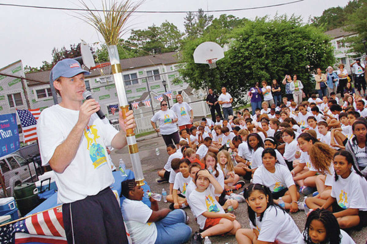 Columbus Magnet School physical education teacher Smith Mowry holds up the torch during the closing ceremony following the school's torch run in recognition of this year's olympics. Hour photo / Erik Trautmann