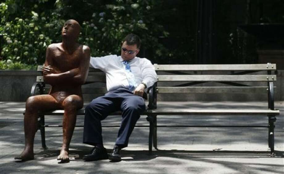 A man takes a nap on a shady park bench next to a sculpture in Dag Hammarskjold Plaza, Wednesday, June 8, 2011 in New York. The official start of summer is still two weeks away, but much of the nation is sweating through near-record temperatures, with heat advisories and warnings issued across the Northeast, mid-Atlantic and upper Midwest on Wednesday. (AP Photo/Mary Altaffer)