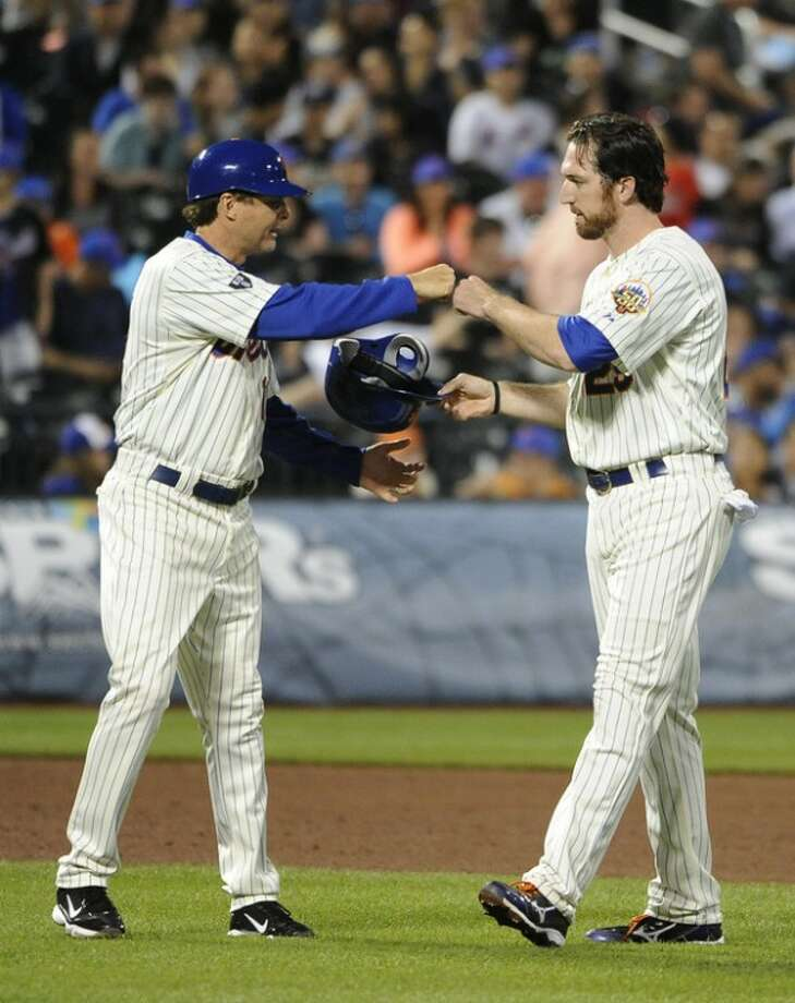 New York Mets third base coachTim Teufel, left, congratulates Ike Davis (29) after Davis hit a two-run single off of San Diego Padres starting pitcher Anthony Bass in the fifth inning of a baseball game on Friday, May 25, 2012, at Citi Field in New York. (AP Photo/Kathy Kmonicek)