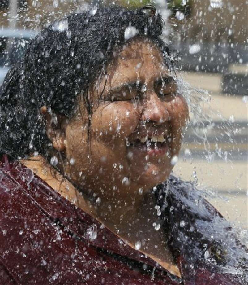 Maria Mejia cools off in a water fountain in Washington, Wednesday, June 8, 2011. The official start of summer is still two weeks away, but much of the nation is sweating through near-record temperatures, with heat advisories and warnings issued across the Northeast, mid-Atlantic and upper Midwest. (AP Photo/Alex Brandon)