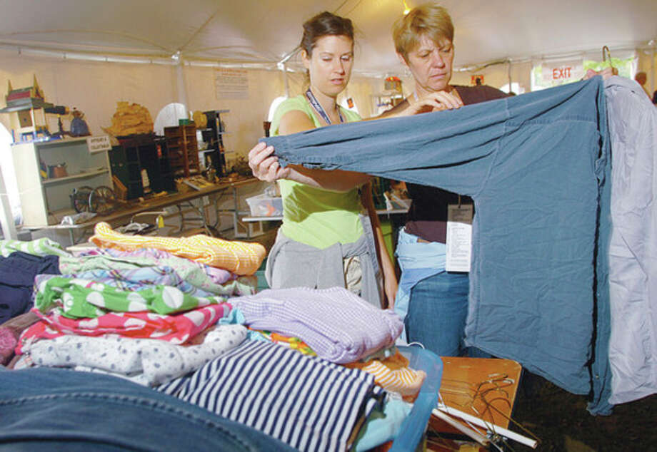 Minks to Sinks volunteer and Family and Children's Agency employees Caroline Tanski and Kim Kristof organize some of the donated items that will available at the annual sale that will benefit FCA and takes place this weekend. Hour photo / Erik Trautmann / (C)2011, The Hour Newspapers, all rights reserved