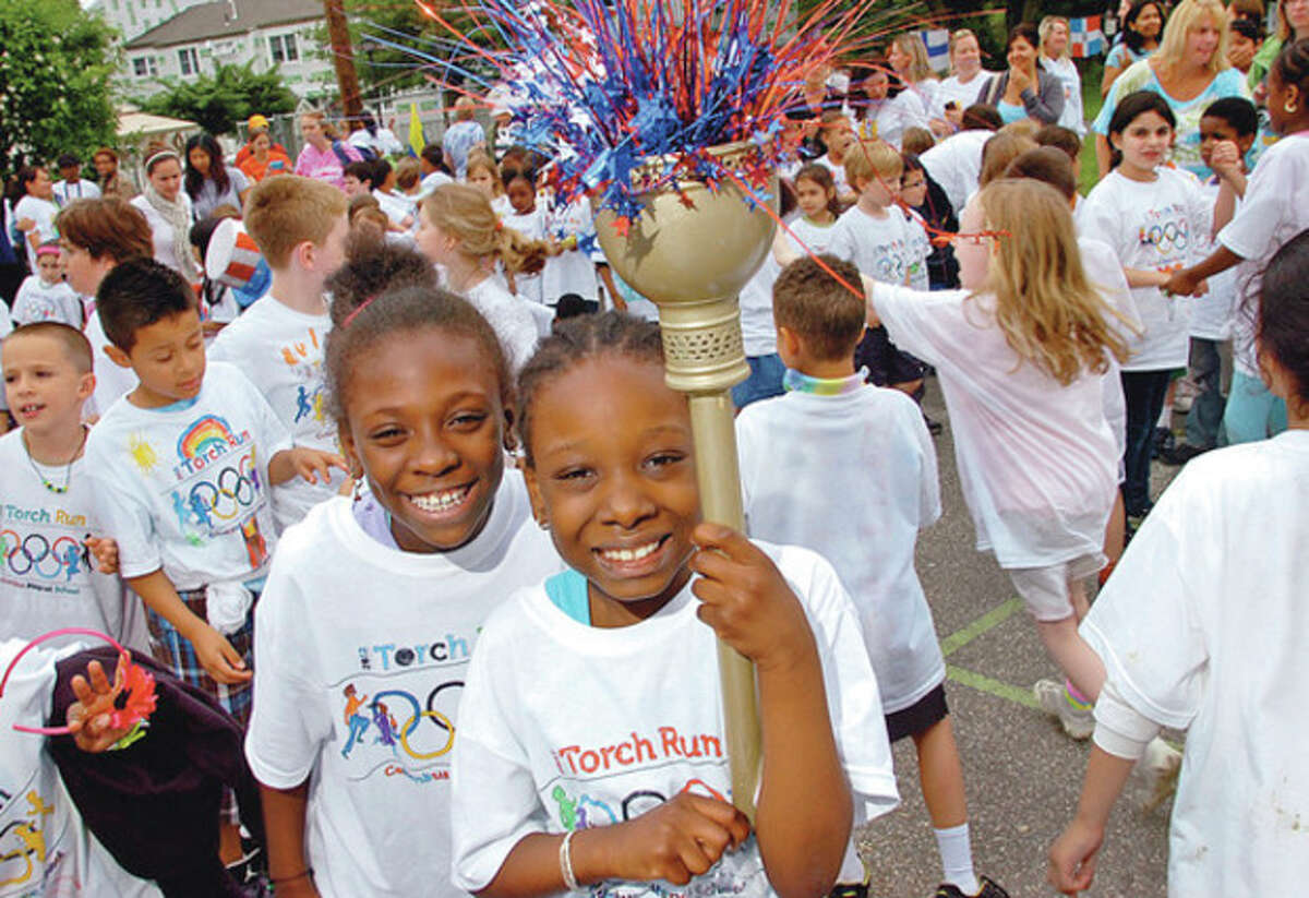 Hour photo / Erik Trautmann Columbus Magnet School second-graders Jordan Kidd and Jennifer Traore hold up a torch during the closing ceremony following the school's torch run in recognition of this year's Olympics.