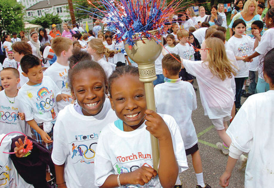 Hour photo / Erik TrautmannColumbus Magnet School second-graders Jordan Kidd and Jennifer Traore hold up a torch during the closing ceremony following the school's torch run in recognition of this year's Olympics. / (C)2012, The Hour Newspapers, all rights reserved