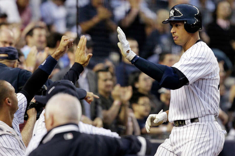 New York Yankees' Alex Rodriguez celebrates with teammates after hitting a third-inning, solo home run during their baseball game against the Kansas City Royals at Yankee Stadium in New York, Wednesday, May 23, 2012. (AP Photo/Kathy Willens) / AP