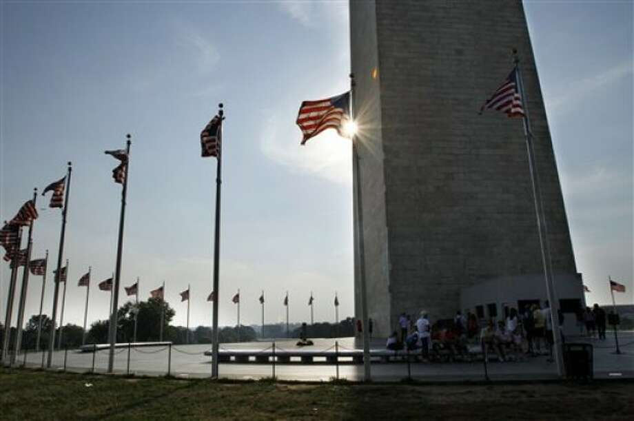 Under a strong sun, people take sheler beneath the shadow of the Washington Monument on the National Mall in Washington, on Wednesday, June 8, 2011. The mercury climbed into the 90s across half the country Wednesday in a record-breaking blast of August-like heat, forcing schools with no air conditioning to let kids go home early and cities to open cooling centers. And scientists say we had better get used to it. (AP Photo/Jacquelyn Martin)
