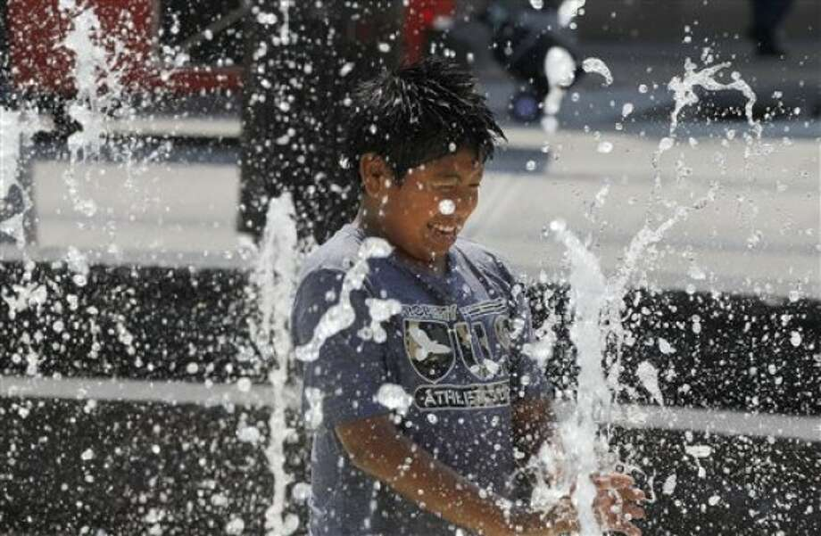 Alexander Reyes, 11, plays in a water fountain in Washington, Wednesday, June 8, 2011. The official start of summer is still two weeks away, but much of the nation is sweating through near-record temperatures, with heat advisories and warnings issued across the Northeast, mid-Atlantic and upper Midwest. (AP Photo/Alex Brandon)