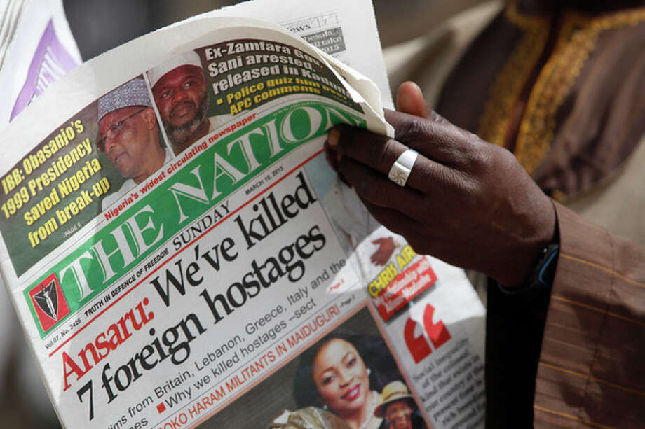 A man reads a local newspapers with the headline 'We've killed 7 foreign hostages' on a street in Kano, Nigeria, Sunday, March. 10, 2013. The United Kingdom's military says its warplanes recently spotted in Nigeria's capital city were there to move soldiers to aid the French intervention in Mali, not to rescue kidnapped foreign hostages. The Ministry of Defense said Sunday that the planes had ferried Nigerian troops and equipment to Bamako, Mali. An Islamic extremist group in Nigeria called Ansaru partially blamed the presence of those planes as an excuse for claiming Saturday that it killed seven foreign hostages it had taken. ( AP Photo/Sunday Alamba) / AP