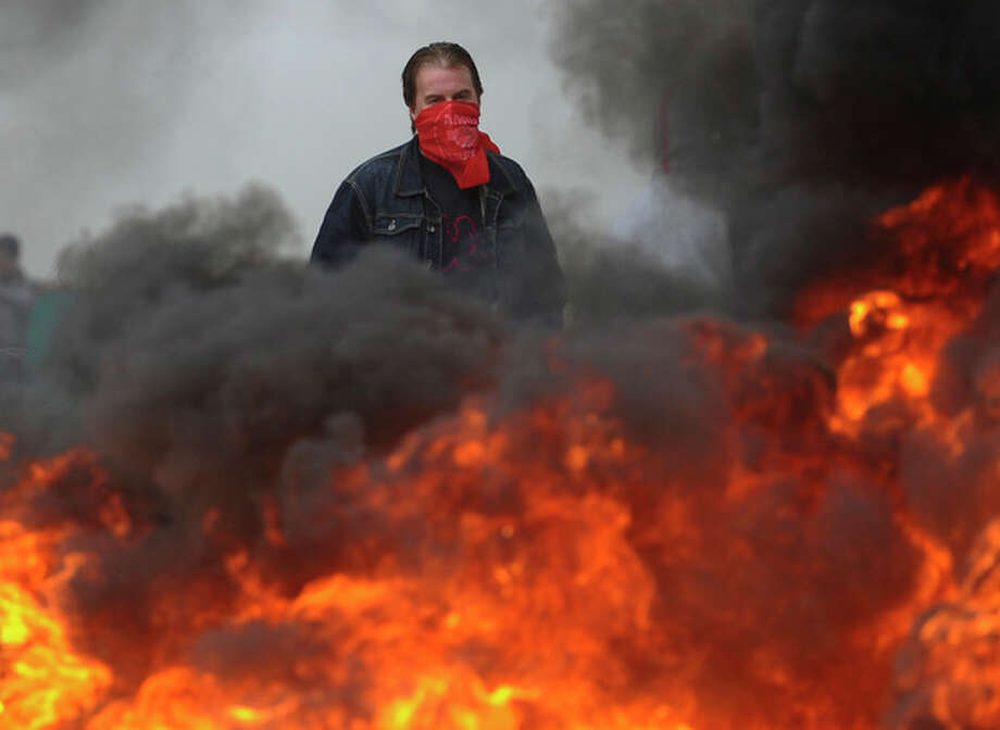 A miner stands behind a burning barricade in Montico, Spain, Thursday, May, 24, 2012. Eight Spanish coal miners are staging a protest underground as part of nationwide strike action by unions opposed to cuts in government subsidies to the sector. General Workers Union mining spokesman Victor Fernandez said some 8,000 workers took part Wednesday in the first of four strike days this month to protest subsidy reductions from euros300 million to euros110 million. Spain is applying across-the-board cutbacks as part of an economy overhaul aimed at slashing its swollen deficit and reducing the country's near 25 percent unemployment rate(AP Photo/Juan Manuel Serrano) / AP