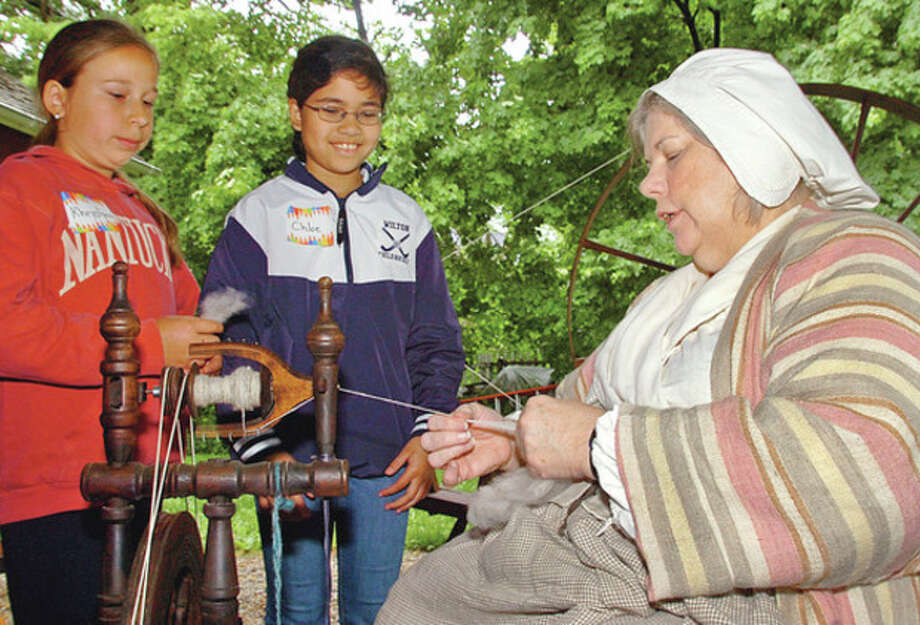 Volunteer Arlene Parkhurst teaches CIder Mill Elementary School 4th graders Christina Barska and Chloe Sokol about spinning wool during the Wilton Historical Society's history immersion program where students recieve hands-on learning on how people lived in colonial times.Hour photo / Erik Trautmann / (C)2012, The Hour Newspapers, all rights reserved