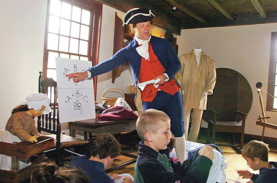 Living Historian Erik Lichak teaches CIder Mill Elementary School 4th graders about needlepoint during the Wilton Historical Society's history immersion program where students recieve hands-on learning on how people lived in colonial times.Hour photo / Erik Trautmann / (C)2012, The Hour Newspapers, all rights reserved