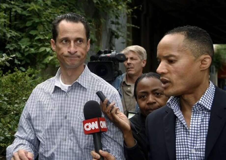 US Congressman Anthony Weiner D-NY, left, leaves his home in New York going to the local laundromat, taking money out of an ATM machine and saying hello at a real estate office before returning to his apartment Saturday, June 11, 2011 (AP Photo/David Karp)