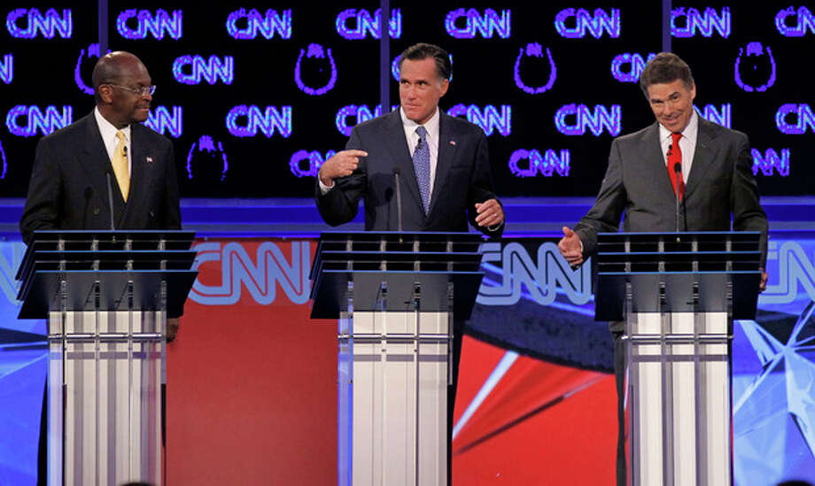 Republican presidential candidates businessman Herman Cain, left, watches as former Massachusetts Gov. Mitt Romney, center, and Texas Gov. Rick Perry speak during a Republican presidential debate Tuesday, Oct. 18, 2011, in Las Vegas. (AP Photo/Chris Carlson) / AP