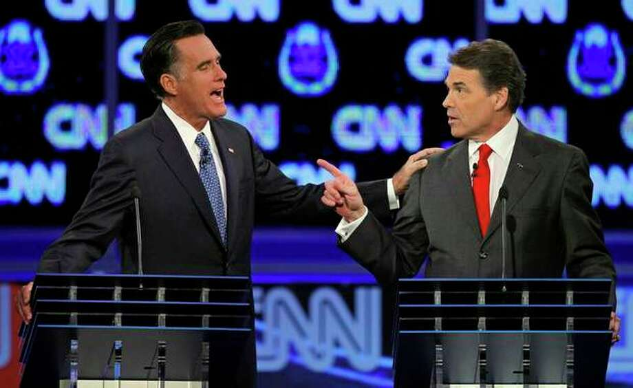 Republican presidential candidates former Massachusetts Gov. Mitt Romney, left, and Texas Gov. Rick Perry speak during a Republican presidential debate Tuesday, Oct. 18, 2011, in Las Vegas. (AP Photo/Chris Carlson) / A